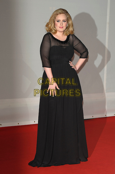 Adele (Adele Laurie Blue Adkins).The Brit Awards 2012 arrivals, O2  Greenwich,  London, England 21st February 2012 .Brits full length black sheer dress hand on hip.CAP/PL.©Phil Loftus/Capital Pictures.