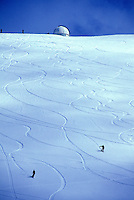 Long range shot of two snowboarders flying down the winter slopes of Mauna Kea creased with multiple tracks. Observatory and blue sky in background.