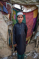 Bangladesh, Cox's Bazar. Kutupalong Rohingya Refugee Camp. The Rohingya, a Muslim ethnic group  denied citizenship in Burma/Myanmar have escaped persecution from Burmese militants in their country. There are up to 500,000 refugees and migrants living in makeshift camps in Cox's Bazar. Muslim boy in front of makeshift home.