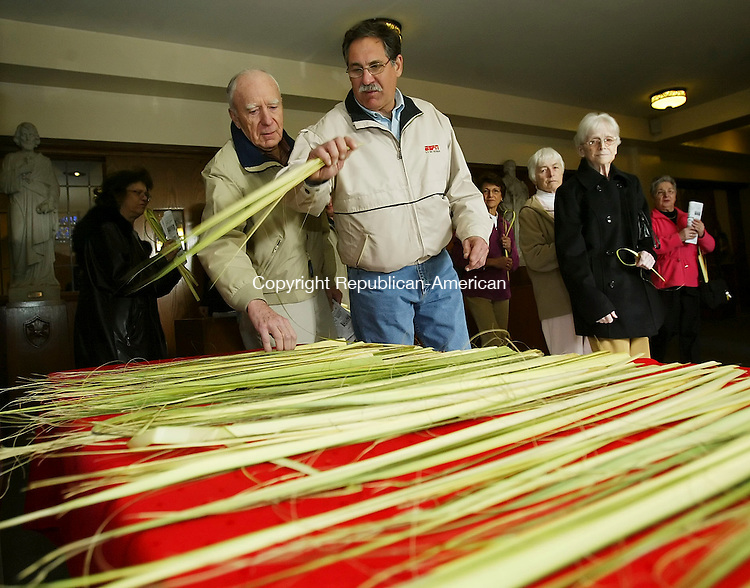 WATERBURY, CT 4/01/07- 040107BZ02- Waterbury residents Robert Brown, left, and Joe Capaldo, take palms from a table after Palm Sunday Mass at SS Peter and Paul Church in Waterbury Sunday.<br /> Jamison C. Bazinet Republican-American
