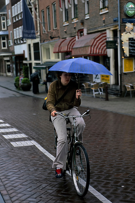 NETHERLANDS, HOLLAND, AMSTERDAM, WOMAN WITH UMBRELLA ON BICYCLE IN RAIN