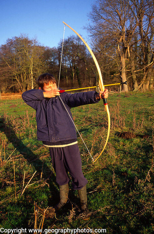 ARM4FD Young boy with bow firing arrow in a field