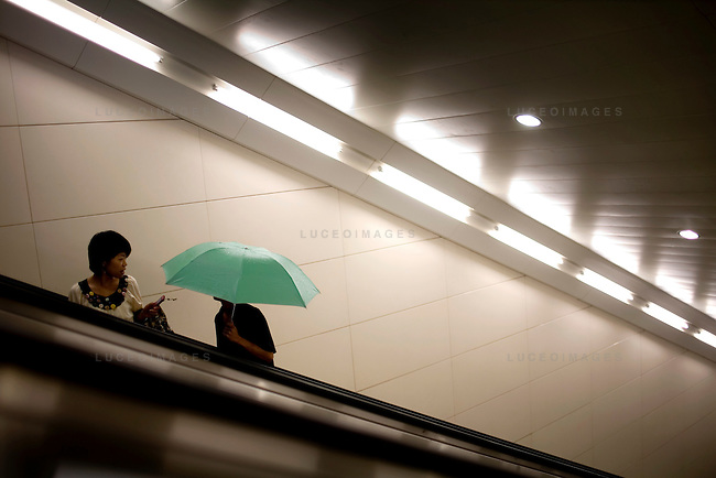 Locals prepare for the rain after riding the subway in Beijing, China on Thursday, August 14, 2008.  Kevin German