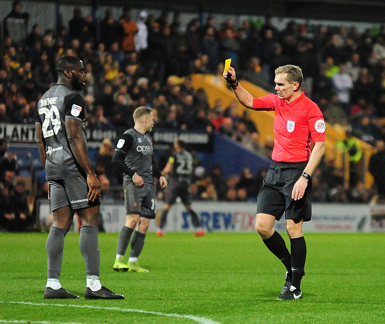 Lincoln City's John Akinde is shown a yellow card by referee Graham Scott<br /> <br /> Photographer Andrew Vaughan/CameraSport<br /> <br /> The EFL Sky Bet League Two - Mansfield Town v Lincoln City - Monday 18th March 2019 - Field Mill - Mansfield<br /> <br /> World Copyright © 2019 CameraSport. All rights reserved. 43 Linden Ave. Countesthorpe. Leicester. England. LE8 5PG - Tel: +44 (0) 116 277 4147 - admin@camerasport.com - www.camerasport.com