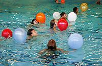 Kinderen watertrappelen met ballonnen. kinderen zwemmen voor een diploma