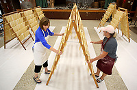 NWA Democrat-Gazette/DAVID GOTTSCHALK   Annette Pianalto (left) and Sara Miller position a rack of fresh pasta noodles Monday, July 10, 2017, at the St. Joseph's Parish Hall in Tontitown. More than 3,000 pounds of pasta noodles are being prepared for the 119th Tontitown Grape Festival which runs Tuesday, August 1 thru Saturday August 5. The homemade spaghetti will be served August 3 thru Aug. 5. For more information see tontitowngrapefestival.com.