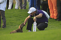 Stray dog is caught by a marshal on the 18th hole during Sunday's Final Round of the 2014 BMW Masters held at Lake Malaren, Shanghai, China. 2nd November 2014.<br /> Picture: Eoin Clarke www.golffile.ie