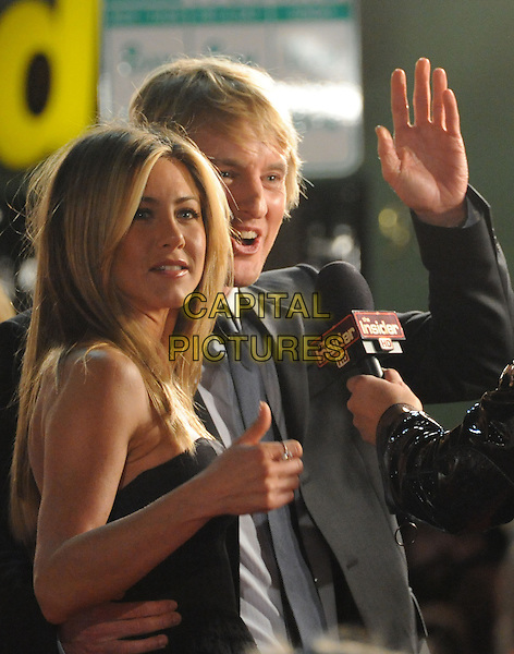 "JENNIFER ANISTON & OWEN WILSON.The Twentieth Century Fox World Premiere of ""Marley & Me"" held at The Mann Village Theatre in Westwood, California, USA. .December 11th, 2008 .half length black grey gray strapless silk satin top suit jacket interview microphone hand palm waving ring  .CAP/DVS.©Debbie VanStory/Capital Pictures."