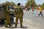 Israeli soldiers watch as Palestinians demonstrate against the planned demolition of houses by the Israeli military in the village of An Nabi Salih near Ramallah on 11/06/2010.