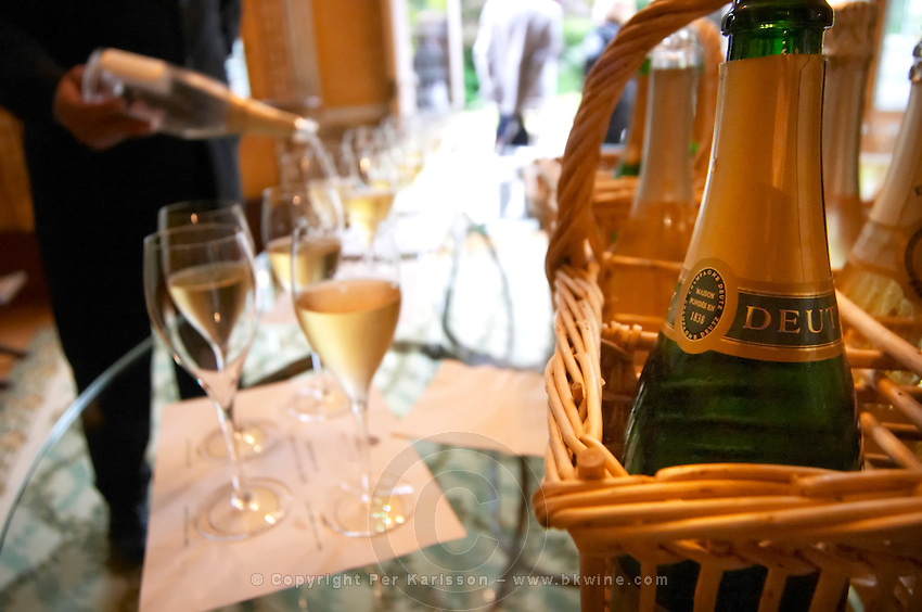 In the tasting room a waiter pouring champagne for a tasting in the background. In the foreground a detail of a bottle of Deutz champagne in a wicker basket at Champagne Deutz in Ay, Vallee de la Marne, Champagne, Marne, Ardennes, France, low light grainy grain