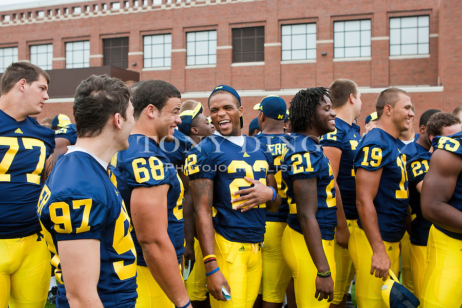 Michigan defensive tackle Mike Martin (68) shares a laugh with wide receiver Darryl Stonum (22) as they wait in line with teammates for photos at the annual NCAA college football media day, Sunday, Aug. 22, 2010, in Ann Arbor, Mich. (AP Photo/Tony Ding)