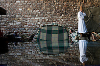 ISTANBUL - MAY 28, 2007:   A man in Ottoman dress stands besides a wall in Istanbul, Turkey. Photo by Landon Nordeman.