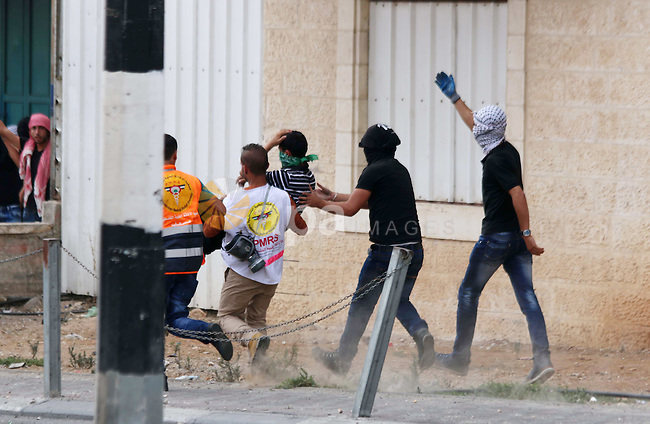 Palestinian protesters carry an injured comrade during clashes with Israeli security forces in the West Bank city of Bethlehem, on October 13, 2015. A wave of stabbings that hit Israel, Jerusalem and the West Bank this month along with violent protests in annexed east Jerusalem and the occupied West Bank, has led to warnings that a full-scale Palestinian uprising, or third intifada, could erupt. The unrest has also spread to the Gaza Strip, with clashes along the border in recent days leaving nine Palestinians dead from Israeli fire. Photo by Muhesen Amren