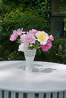 Cut flower arrangement of Paeonia peonies in vase on table mixed varieties white, pink