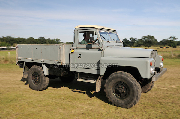 "1962 Land Rover 129in prototype 2.5 Turbo Diesel on 11.00 x 16 wheels. Dunsfold Collection of Land Rovers Open Day 2011, Dunsfold, Surrey, UK. --- No releases available, but releases may not be necessary for certain uses. Automotive trademarks are the property of the trademark holder, authorization may be needed for some uses. --- Vehicle Information: Vehicle belongs to the Dunsfold Collection of Land Rovers: Chassis number 129/5, Registration FYF 928C, Engine 2.5 turbo diesel intercooler, Gearbox  4-speed manual plus remote transfer box. --- Vehicle History: This was one of five prototypes built for military trials for the Belgium Army in the early sixties. One other survives at Gaydon, a six cyl type with an early style body. The load capacity is 35cwt, which with the drop side body made this, a very useful little truck. The engine was a bored out 2.25 with a 5 main bearing crank and a C.A.V. turbo and intercooler set up. A four-speed crash box with a much larger oil capacity is coupled up to a special remote transfer box with a tyre inflation set up. The axles are Timken made with the only Land Rover part on the axles being the rear wheel cylinders. ""Lofty"" was found in a scrap yard in hounslow in 1968 and was snapped up making this the second collection vehicle to be saved. It had a minor preservation some years ago and was put back into its original grey paint. The 11.00x16 tyres are the original type used when new."