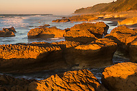 Sunset on rocky beach with limestone formations at Paturau on west coast of South Island, Nelson Region, New Zealand