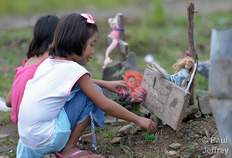 A girl arranges items marking the grave of a friend in a church yard in the city of Palo, in the Philippines province of Leyte, where typhoon Haiyan killed hundreds of people in November 2013. The storm was known locally as Yolanda.