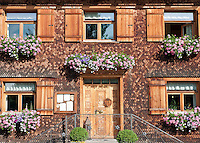 Austria, Vorarlberg, Krumbach: Inn Adler, facade with wood shingles and flower boxes | Oesterreich, Vorarlberg, Krumbach: Gasthof Adler, Wandverkleidung mit Holzschindeln in der Form von Biberschwanzziegeln
