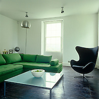 Wrapping around the family room is a capacious green sofa by Ligne Roset and in the corner stands a black leather Egg chair by Arne Jacobsen