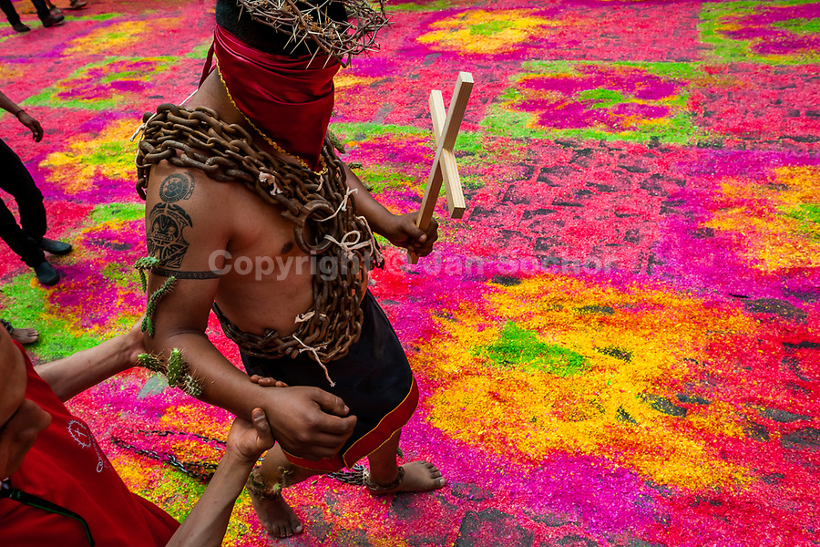 A hooded penitent, wearing chains and cactus spines stuck to his arm, walks on a colorful sawdust carpet during the Holy week procession in Atlixco, Mexico, 30 March 2018. Every year on Good Friday, dozens of anonymous men of all ages voluntarily undergo pain and suffering during the religious procession of the 'Engrillados' (the Shackled ones) in Puebla state, central Mexico. Wearing heavy chains on their shoulders covered with prickling cacti while being burned by the hot midday sun, they recall Jesus Christ's death by crucifixion and demonstrate their religiosity and faith.