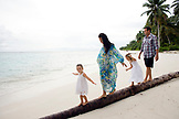 INDONESIA, Mentawai Islands, Kandui Resort, family walking and balancing on a fallen palm tree