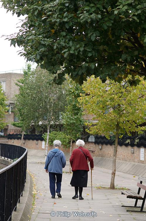 Two elderly women walk along a canal towpath in Paddington, London.