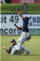 Hagerstown Suns shortstop Osvaldo Abreu (10) collides with left fielder Bryan Mejia (12) after catching a fly ball during the game against the Kannapolis Intimidators at CMC-Northeast Stadium on July 19, 2015 in Kannapolis, North Carolina.  The Suns defeated the Intimidators 9-4.  (Brian Westerholt/Four Seam Images)