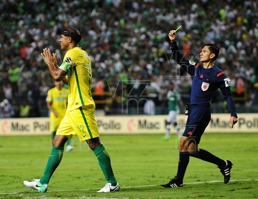 PALMIRA -COLOMBIA-14-06-2017. Mario Herrera, árbitro, muestra la tarjeta amarilla a Alexis Henriquez del Nacional durante el partido de ida entre el Deportivo Cali y Atletico Nacional por la final de la Liga Aguila I 2017 jugado en el estadio Palmaseca de Cali. / Mario Herrera, referee, shows the yellow card to Alexis Henriquez o Nacional during the first leg match between Deportivo Cali and Atletico Nacional for the final of the Aguila League I 2017 played at Palmaseca stadium in Cali.  Photo: VizzorImage/ Nelson Rios /Cont
