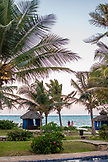 ZANZIBAR, Bwejuu Beach, a young couple at the Palms Resort, next to blue beach huts and Palm Trees