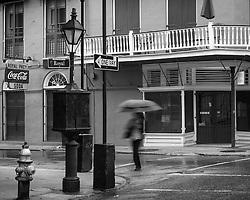A figure walks down Royal Street in the rain.