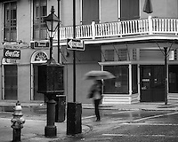 A figure walks down Royal Street in the rain.