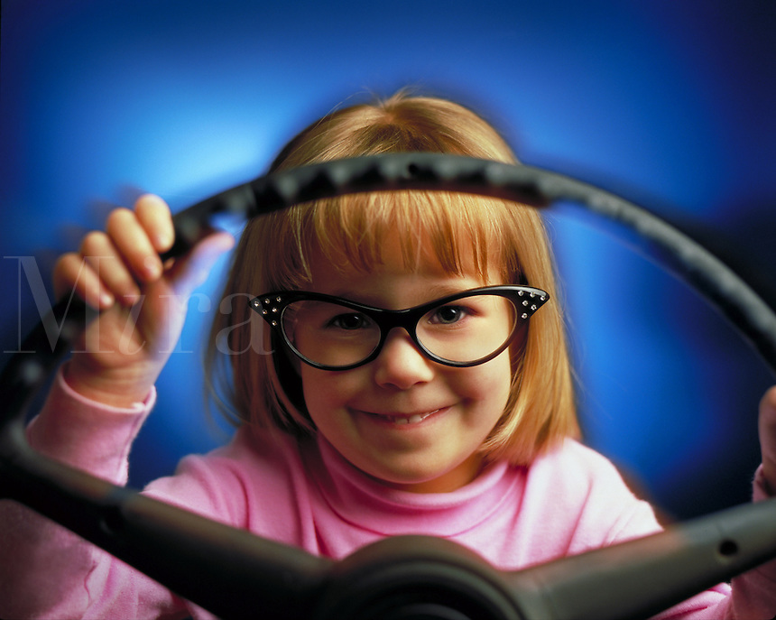 Little girl with funny glasses sits behind the steering wheel of a car, pretending to drive.