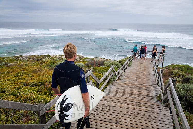 A surfer walks down to Surfer's Point, a popular break known locally as Margaret's.  Margaret River, Western Australia, AUSTRALIA.