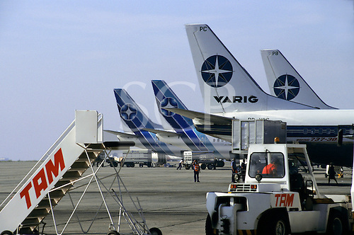 Rio de Janeiro, Brazil. Varig and RioSul airplane tailplanes with a TAM tractor and gangway, Galeao Airport.
