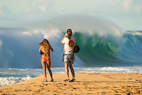 Tourist couple taking pictures of large waves on the north shore of Oahu.