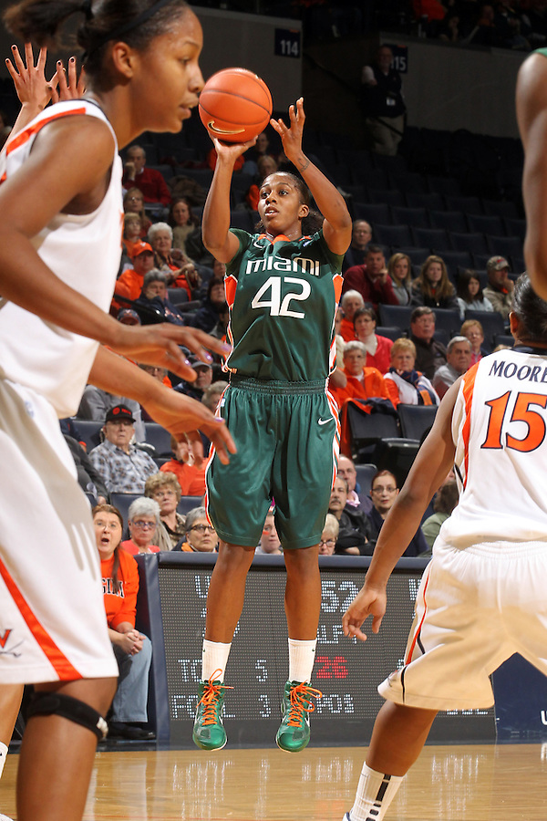 Jan. 6, 2011; Charlottesville, VA, USA; Miami Hurricanes guard Shenise Johnson (42) shoots between Virginia Cavaliers defenders during the game at the John Paul Jones Arena.  Mandatory Credit: Andrew Shurtleff