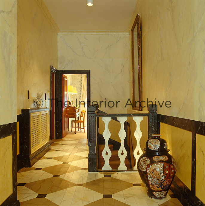 A large Japanese porcelain urn stands in a corner of this landing which has a painted floor and marbleised walls
