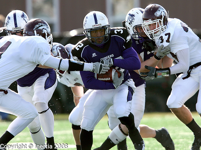 SIOUX FALLS, SD - NOVEMBER 15:  Lavell Jackson #32 of the University of Sioux Falls scampers through a pair of defenders Ryan Klein #4 and Tucker Tejkl #37 of Morningside on a punt return during the first quarter Saturday afternoon at the USF Athletic Complex. (Photo by Dave Eggen/Inertia)