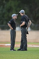 Umpire John Budka Jr. (left) discusses a call with home plate umpire Will Robinson during the Coastal Plain League game between the Asheboro Copperheads and the High Point-Thomasville HiToms at Finch Field on June 12, 2015 in Thomasville, North Carolina.  The HiToms defeated the Copperheads 12-3. (Brian Westerholt/Four Seam Images)