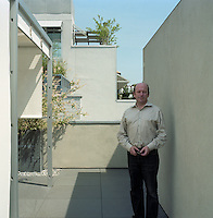 Nico Rensch photographed on a secluded terrace screened by a tall partition which is rendered in dove-grey plaster