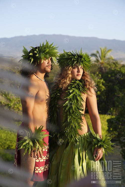 Kane (male) and wahine (female) hula dancers deep in thought, wearing palapalai fern head lei, headshot.