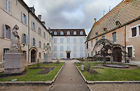 Cour des Fondateurs or Courtyard of the Founders, with statues of founders Nicolas Rolin, chancellor of Burgundy, and his wife Guigone de Salins, 1914-23, by Henri Bouchard, at Les Hospices de Beaune, or Hotel-Dieu de Beaune, a charitable almshouse and hospital for the poor, built 1443-57 by Flemish architect Jacques Wiscrer, in Beaune, Cote d'Or, Burgundy, France. To the right is an ornate rooftop with Burgundian glazed tiles in geometric patterns. The hospital was run by the nuns of the order of Les Soeurs Hospitalieres de Beaune, and remained a hospital until the 1970s. The building now houses the Musee de l'Histoire de la Medecine, or Museum of the History of Medicine, and is listed as a historic monument. Picture by Manuel Cohen