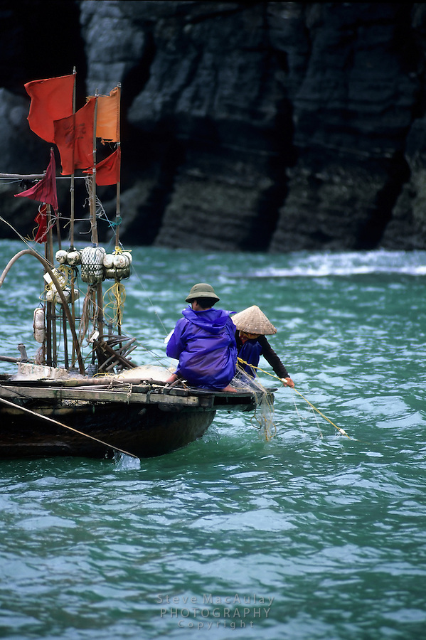 Vietnamese fishermen tending there nets, Halong Bay, Vietnam