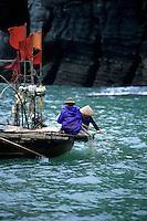 Vietnamese fishermen tending there nets, Halong Bay, Vietnam
