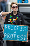 © Joel Goodman - 07973 332324 . 26/08/2017. Manchester , UK. PRIDE IS PROTEST placard . 2017 Pride parade through Manchester City Centre . The annual festival , which is the largest of its type in Europe , celebrates LGBT life . Photo credit : Joel Goodman