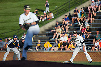 Wake Forest Demon Deacons first baseman Gavin Sheets (24) holds runner Cole Austin (28) of the West Virginia Mountaineers as starting pitcher Parker Dunshee (36) delivers a pitch to the plate in Game Four of the Winston-Salem Regional in the 2017 College World Series at David F. Couch Ballpark on June 3, 2017 in Winston-Salem, North Carolina.  The Demon Deacons walked-off the Mountaineers 4-3.  (Brian Westerholt/Four Seam Images)