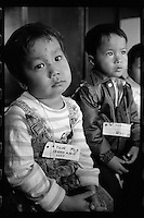 Vietnamese refugee boys wait for free hair cut at a boat people camp in Hong Kong. Tens of thousands of Vietnamese refugees fled the Communist regime by boats to Hong Kong in 1980s.