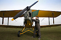 13/03/15<br /> <br /> Colin Temple-Smith prepares the restored Tiger Moth for its first flight.<br /> <br /> ***FULL STORY HERE:   http://www.fstoppress.com/articles/tiger-moth-restorations/    ****<br /> <br /> You may remember spending hours toiling over Airfix models, painstakingly following intricate instructions and trying not to glue your fingers together before painting your own miniature version of one of the RAF&rsquo;s or Luftwaffe&rsquo;s finest aircraft. Then spare a thought for one man who has just helped to restore and put together one World War Two Tiger Moth and is about to start piecing together another FOUR aircraft that were discovered in bits in a barn.<br /> <br /> Sixty-year-old Colin Temple-Smith &ndash; who wears a moustache that any Wing Commander would be proud of &ndash; has spent a lifetime restoring vintage cars and motorcycles and recently quit his job as a window fitter to help re-build the five bi-planes that will become part of a growing fleet of Tiger Moths at Derbyshire based Blue Eye Aviation.<br /> <br /> Today saw the first of the fully-restored five aircraft take to the skies.<br /> <br /> &ldquo;It&rsquo;s just like working on old bikes and cars, although they&rsquo;re a lot more fragile&rdquo; explained Colin, whose wife runs the Aviators Caf&eacute; at Darley Moor Airfield near Ashbourne.<br /> <br /> &ldquo;When I was a teenager I used to be a member of a modelling club, making flying models from wood and canvas. They&rsquo;re very similar to build &ndash; it&rsquo;s really just the size that&rsquo;s changed with these.<br /> <br /> All Rights Reserved: F Stop Press Ltd. +44(0)1335 418629   www.fstoppress.com.