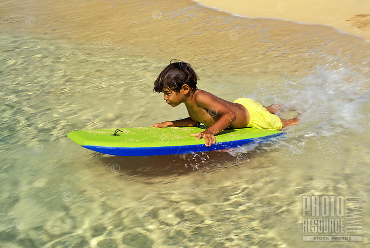 Boy boogieboarding near shoreline