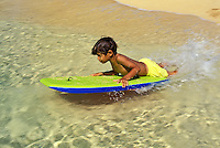 Boy boogieboarding near shoreline